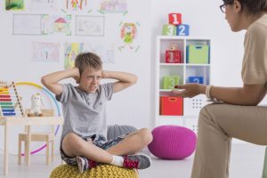 Self Regulation and Alertness Angry kid covering his ears during therapy with in room with toys